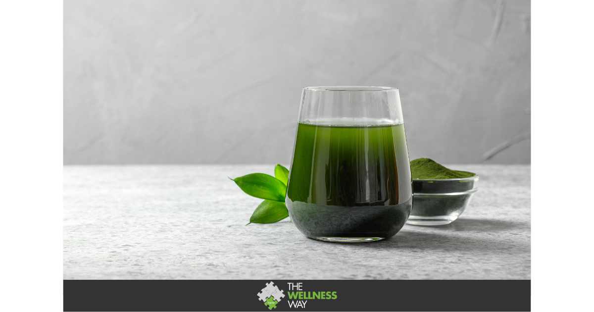 a glass filled with dark green liquid on a grey cloth with a grey background.