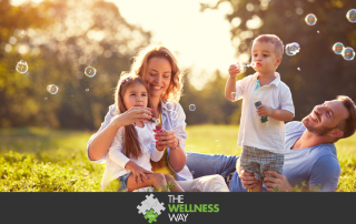 a family of parents and two children sitting in a field of grass and blowing bubbles together.