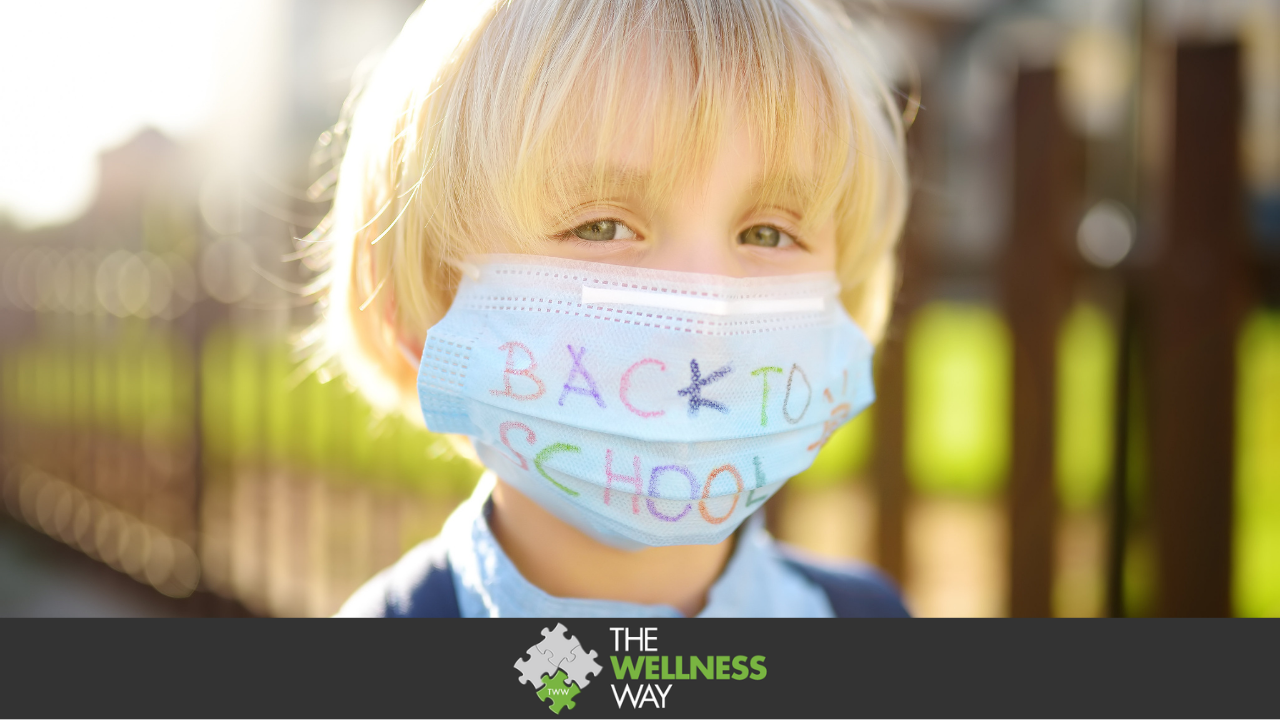"""A young, blonde-haired boy wearing a surgical mask with the words """"back to school"""" written on the mask in marker"""