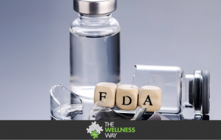 One vial is broken with blocks with the letters FDA laying inside. A full vaccine vial is behind it on a grey background.