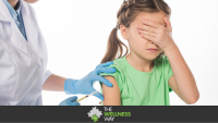 Pediatrician doing injection with vaccine to scared child isolated on white