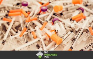 a pile of medical syringes and vaccine vials on a white background