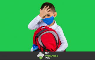 a young school boy holding a backpack, with his hand to his forehead and wearing a mask against a green background